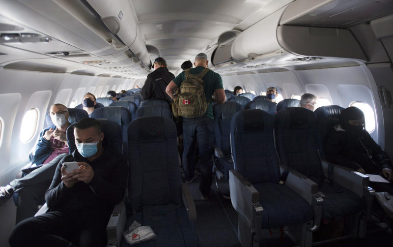 Passengers wear protective face masks and are physically distanced on a flight from Calgary to Vancouver, Tuesday, June 9, 2020. Airlines in Canada and around the world are suffering financially due to the lack of travel and travel bans due to COVID-19. (Jonathan Hayward/The Canadian Press via AP)