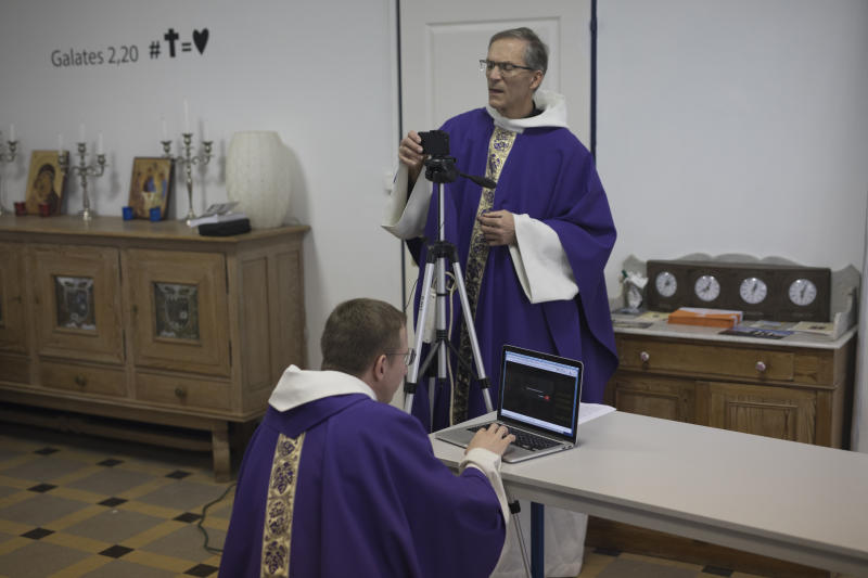 Priest Philippe Rochas, left, and Jean-Benoit de Beauchene pack up livestreaming equipment after holding a closed door Sunday mass at the St. Vincent de Paul church in Marseille, southern France, Sunday, March 22, 2020. As mass gatherings are forbidden due to measures to prevent the spread of COVID- 19, priests are using technology to reach worshippers forced to stay at home. For most people, the new coronavirus causes only mild or moderate symptoms. (AP Photo/Daniel Cole)