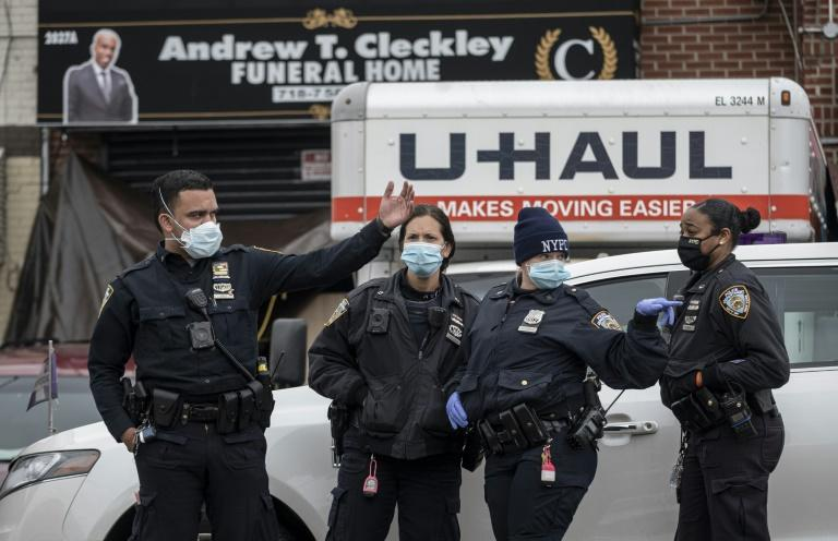 Police stand in front of a funeral home in Brooklyn on April 30, 2020 after dozens of bodies were found decomposing in trucks