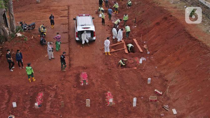 Petugas melakukan proses pemakaman jenazah dengan menerapkan protokol Covid-19 di TPU Pondok Ranggon, Jakarta Timur, Minggu (27/9/2020). Dinas Bina Marga DKI Jakarta akan membuka lahan pemakaman baru seluas 7.141 meter persegi pada tahap pertama. (Liputan6.com/Herman Zakharia)