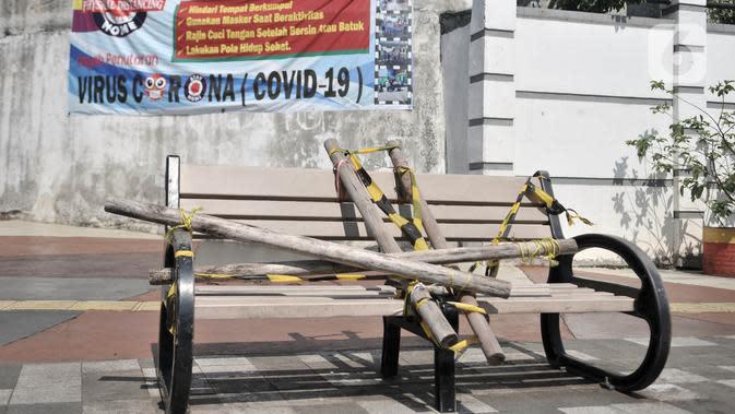 Kondisi bangku trotoar yang disegel garis pembatas dan ditutupi bambu di kawasan Rawamangun Jakarta, Minggu (3/5/2020). Bangku trotoar di sepanjang jalan Rawamangun disegel untuk mencegah kerumunan warga sebagai upaya memutus rantai penyebaran COVID-19. (merdeka.com/Iqbal S. Nugroho)