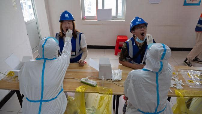 Staf medis mengambil sampel usap tenggorokan dari para pekerja konstruksi di lokasi pengambilan sampel sementara di Distrik Daxing, Beijing, China (2/7/2020). Sebanyak 1.353 pekerja di lokasi konstruksi tersebut menjalani pengambilan sampel tes asam nukleat pada Kamis (2/7). (Xinhua/Cai Yang)