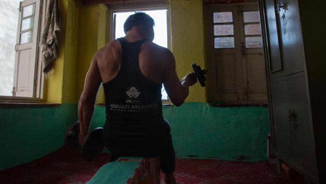 Atlet angkat besi Kashmir, Bashir Ahmed melakukan latihan di rumahnya di Srinagar pada 21 April 2020. Seperti atlet yang lain, Ahmed harus menjalani latihan di rumah, namun lockdown bagi 7 juta penduduk Kashmir bukan hal yang baru. (AP Photo/Dar Yasin)