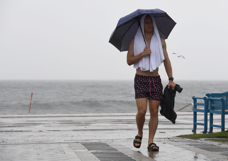 A pedestrian holds an umbrella during heavy rain in Coogee, Sydney