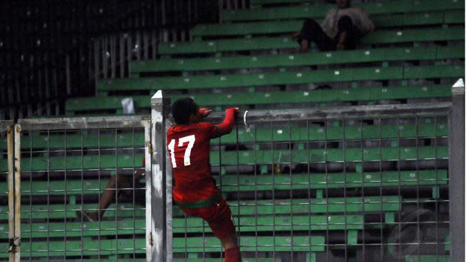 Ferdinand Sinaga memanjat pagar pembatas Stadion Utama Gelora Bung Karno, (11/5/2015). (Liputan6.com/Helmi Fithriansyah)