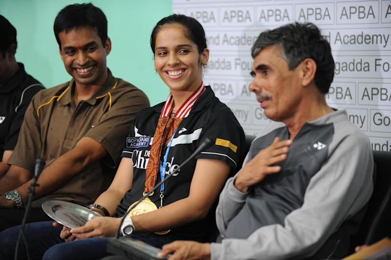 Indian badminton player Saina Nehwal (C) shares a light moment with her coach P. Gopichand (L) and her father Harvir Singh as they address media representatives at a press conference in Hyderabad on June 29, 2010. Nehwal, who rounded a hat-trick of Super Series titles by succesfully defending her Indonesia Open Super Series trophy in Jakarta on June 27, said she would now have to work harder to improve her ranking from number three to one. Nehwal defeated Japanese opponent Sayaka Sato 21-19, 13-21, 21-11. to win her latest title in the Indonesian capital. AFP PHOTO/Noah SEELAM (Photo credit should read NOAH SEELAM/AFP/Getty Images)
