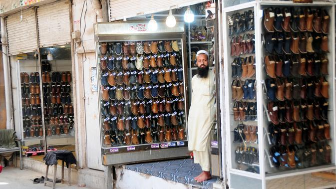 Seorang pedagang asal Pakistan menjual sepatu tradisional yang dikenal sebagai