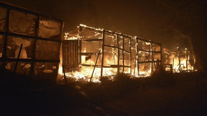 Api membakar tenda darurat di kamp pengungsi Moria, Yunani, Rabu (9/9/2020). Kamp Moria ditempati lebih dari 12.500 pengungsi dan imigran. Sebagian besar dari mereka tiba di Moria antara tahun 2015 dan 2016, usai melarikan diri dari rumah di Irak dan Suriah. (AP Photo/Panagiotis Balaskas)