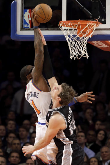 New York Knicks forward Amare Stoudemire (1) tips the ball in over the defense of San Antonio Spurs forward Tiago Splitter (22) in the first half of their NBA basketball game at Madison Square Garden in New York, Thursday, Jan. 3, 2013. (AP Photo/Kathy Willens)