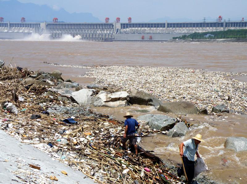 Two workers clean up trash along the bank of the Yangtze River near the Three Gorges Dam in Yichang, in central China's Hubei province on August 1, 2010. Layers of trash floating in the Yangtze river are threatening to jam China's massive Three Gorges hydroelectric dam, state media reported on August 2. CHINA OUT AFP PHOTO (Photo credit should read STR/AFP/Getty Images)