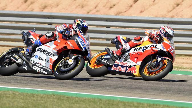 Momen saat pembalap Repsol Honda, Marc Marquez beradu kecepatan dengan pembalap Ducati, Andrea Dovizioso pada MotoGP Aragon 2018. (JOSE JORDAN / AFP)