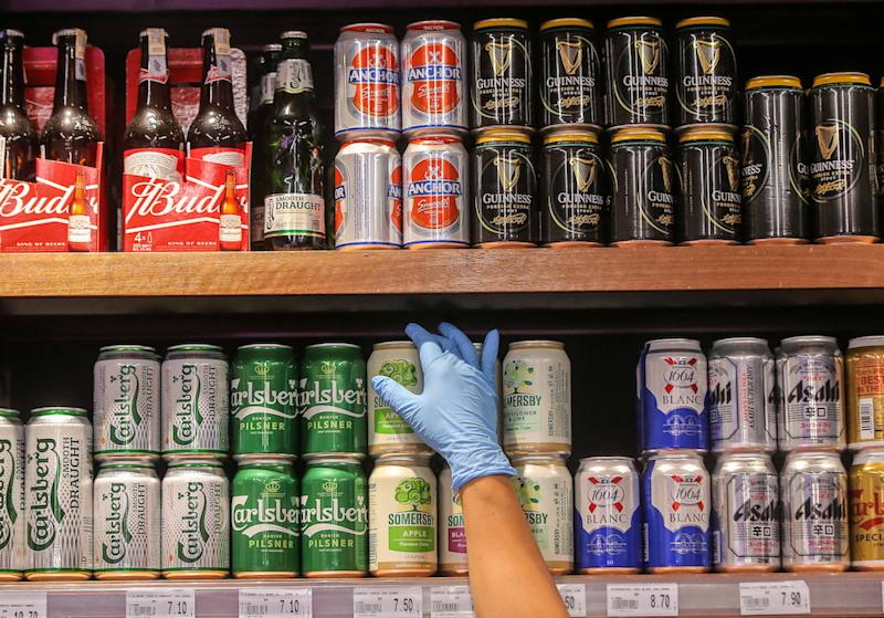 A Jaya Grocer staff arranging cans of beer in Ipoh. — Picture by Farhan Najib