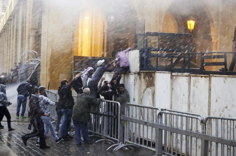 Lebanese protesters try to scale barricades blocking access to the parliament building in central Beirut as security forces spray them with water cannons
