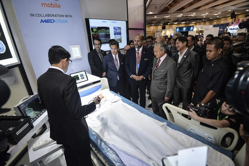 Prime Minister Tun Dr Mahathir Mohamad looks on as a representative at the U Mobile booth explains how the 5G technology can assist in the advancement of medical procedures. — Picture by Mukhriz Hazim