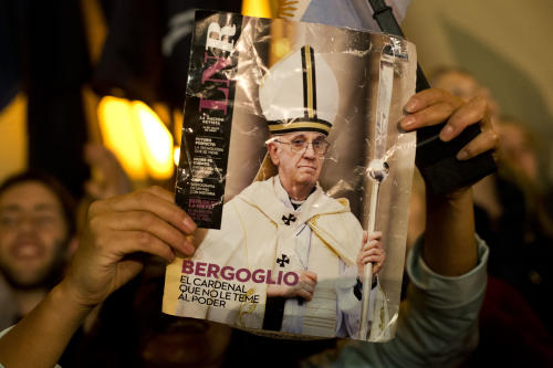 "A worshiper holds up the front page of a magazine showing a photograph of Jorge Mario Bergoglio with the title in Spanish ""Bergoglio. The cardinal who isn't afraid to face power"" during celebrations outside the Metropolitan Cathedral in Buenos Aires, Argentina, Wednesday, March 13, 2013. Latin Americans reacted with joy on Wednesday at news that Bergoglio was elected pope. Bergoglio, who chose the name Pope Francis, is the first pope ever from the Americas. (AP Photo/Victor R. Caivano)"