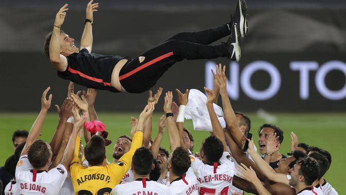 Pemain Sevilla mengangkat sang pelatih, Julen Lopetegui, usai mengalahkan Inter Milan pada laga final Liga Europa 2019/2020 di Stadion RheinEenergie, Sabtu (22/8/2020) dini hari WIB. Sevilla menang 3-2 atas Inter Milan. (AFP/Friedemann Vogel/pool)