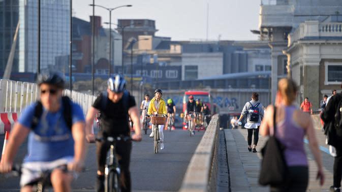 Pesepeda dan pejalan kaki melintasi London Bridge menuju Kota London di Inggris, Selasa (15/9/2020). Tingkat pengangguran di Inggris meningkat menjadi 4,1 persen dalam tiga bulan hingga Juli dari 3,9 persen pada periode April-Juni, kata Kantor Statistik Nasional. (JUSTIN TALLIS/AFP)