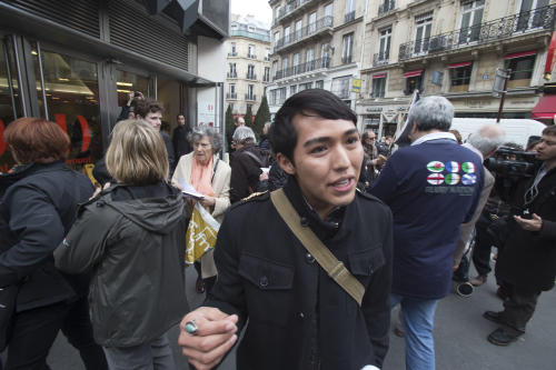 An American exchange student, member of the Hopi tribe, Bo Lomahquahu, speaks to the media as he protests outside of the Druout's auction house to protest the auction of Native American Hopi tribe masks in Paris, Friday, April 12, 2013. A contested auction of dozens of Native American tribal masks went ahead Friday afternoon following a Paris court ruling, in spite of appeals for a delay by the Hopi tribe, its supporters including actor Robert Redford, and the U.S. government. (AP Photo/Michel Euler)