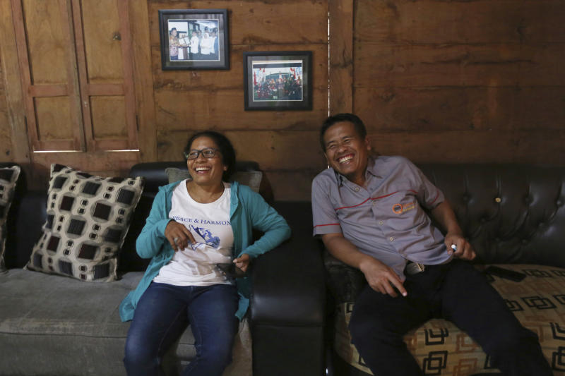 Ni Luh Erniati, left, laughs with Ali Fauzi during her visit to Fauzi's house in Tenggulun, East Java, Indonesia, on Saturday, April 27, 2019. Erniati, whose husband was killed in the 2002 Bali bombings, and Fauzi, a former bombmaker whose brothers helped orchestrate the Bali attack, have reconciled as part of a peacebuilding program bringing together ex-terrorists and victims. (AP Photo/Tatan Syuflana)
