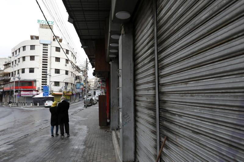 FILE PHOTO: People walk next to closed shops in Amman