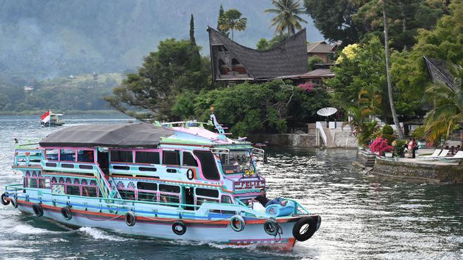 Gambar pada 3 April 2019 menunjukkan sebuah kapal wisata tiba di Pulau Samosir, pulau vulkanik di tengah Danau Toba, provinsi Sumatera Utara, 3 April 2019. Di kalangan masyarakat Batak sendiri, Danau Toba ibaratnya inang atau ibu yang akan selalu menanti dengan keindahannya. (GOH CHAI HIN / AFP)