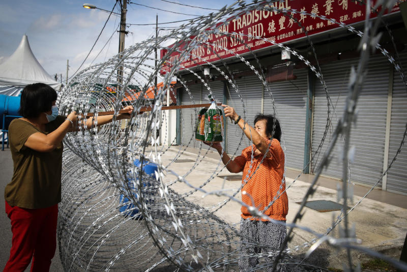 Retiree Wong Ai Kwok (right) collects supplies through barbed wire fencing in PJ Old Town, Petaling Jaya May 12, 2020. — Picture by Yusof Mat Isa