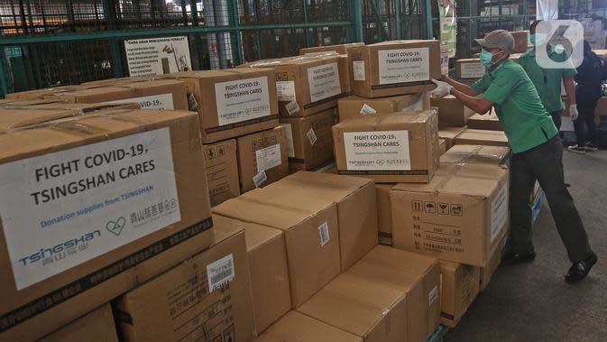 Petugas merapikan karton berisi alat kesehatan bantuan investor China di Terminal Kargo 530 Bandara Internasional Soekarno Hatta, Jumat (27/3/2020). Bantuan terdiri dari test kit COVID-19, swab kit, masker, hingga alat pelindung diri (APD). (Liputan6.com/Herman Zakharia)