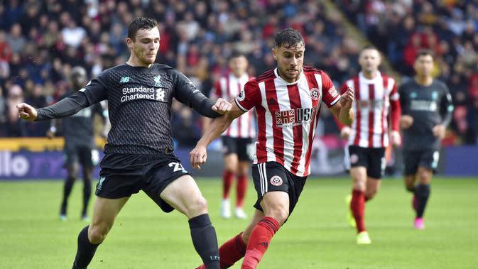 Bek Liverpool, Andrew Robertson, berebut bola dengan pemain Sheffield United, George Baldock, pada laga Premier League di Stadion Bramall Lane, Sabtu (28/9). Liverpool menang 1-0 atas Sheffield United. (AP/Rui Vieira)
