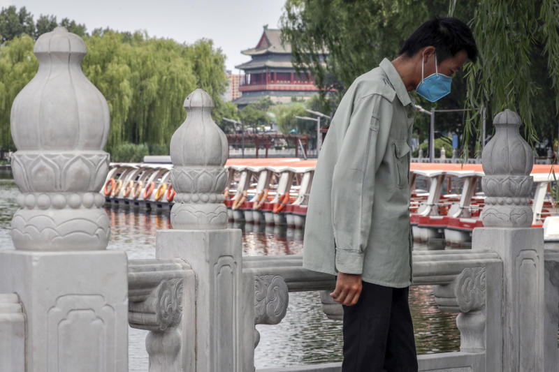 A man wearing a protective face mask to help curb the spread of the coronavirus stands against a roll of boats parked on the barricaded Houhai Lake, a usually popular tourist spot before the new coronavirus outbreak in Beijing, Tuesday, June 30, 2020. China, where the coronavirus pandemic began in December, was the first economy to reopen in March after the ruling Communist Party declared victory over the disease. Manufacturing and other activity is reviving but demand for exports is feeble and Chinese consumers, worried about losing jobs, are reluctant to spend. (AP Photo/Andy Wong)