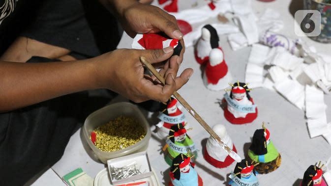 Pekerja membuat ondel-ondel dari shuttlecock atau kok bekas di perkampungan Budaya Betawi, Srengseng Sawah, Jakarta, Sabtu (8/8/2020). Pembuatan ondel-ondel dari shuttlecock bekas mampu memproduksi hingga 100 buah per harinya. (Liputan6.com/Fery Pradolo)