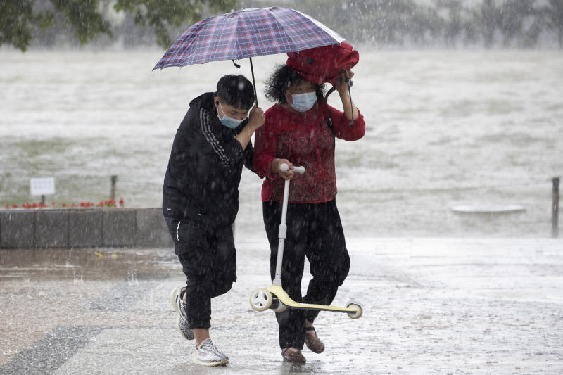 Visitors wearing masks to curb the spread of the coronavirus takes shelter from a sudden rainstorm at a park in Beijing on Saturday, May 23, 2020. New coronavirus cases dropped to zero in China for the first time Saturday but overwhelmed hospitals across Latin America – both in countries lax about lockdowns and those lauded for firm, early confinement. (AP Photo/Ng Han Guan)