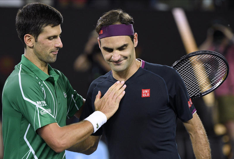 FILE - In this Jan. 30, 2020, file photo, Switzerland's Roger Federer, right, congratulates Serbia's Novak Djokovic on winning their semifinal match at the Australian Open tennis championship in Melbourne, Australia. (AP Photo/Andy Brownbill, File)