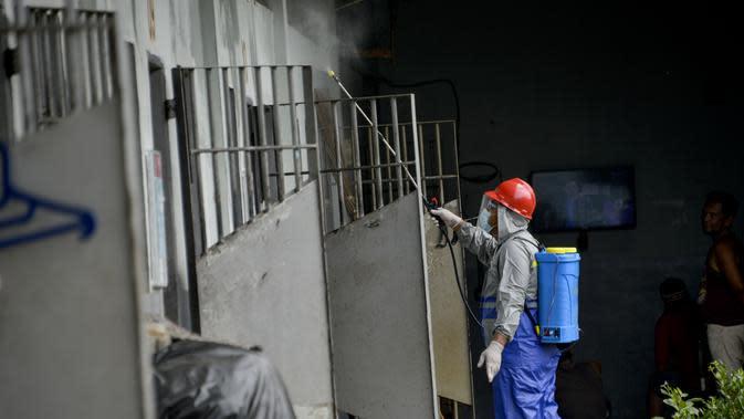 Seorang narapidana (kiri) menyemprotkan disinfektan sebagai bagian dari upaya penanggulangan virus corona COVID-19 di sebuah penjara di Banda Aceh (3/9/2020). (AFP Photo/Chaideer Mahyuddin)