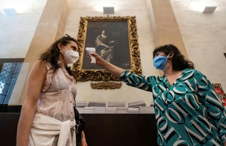 A journalist gets her temperature checked at the Uffizi Gallery Museum in Florence
