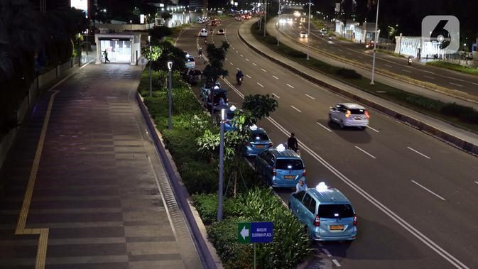 Deretan taksi konvensional menanti penumpang di Jalan Jenderal Sudirman, Jakarta, Kamis (2/4/2020). Pemerintah menetapkan Pembatasan Sosial Berskala Besar dengan membatasi kegiatan tertentu penduduk di wilayah yang diduga terinfeksi COVID-19. (Liputan6.com/Helmi Fithriansyah)
