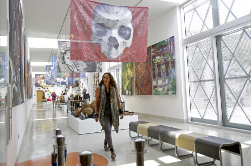 Fashion designer Donna Karan walks through the art gallery during her visit to Little Haiti at the Discover Haiti Exhibition in Miami, Friday, May 17, 2013. Karan is among the designers and celebrities who have advocated for Haitian artisans since a catastrophic earthquake shook the Caribbean country in 2010. (AP Photo/Alan Diaz)