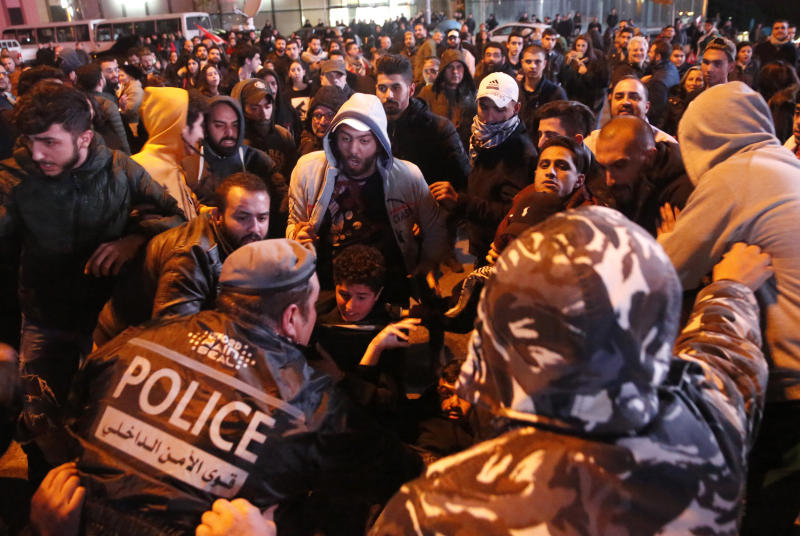 Lebanese policemen try to remove anti-government protesters to reopen a main road that was closed during ongoing protests against the ruling elite of corruption and financial crisis, in Beirut, Lebanon, Monday, Jan. 13, 2020. Lebanon is facing its worst economic crisis in decades, while protests against corruption and mismanagement have gripped the country since October. (AP Photo/Hussein Malla)