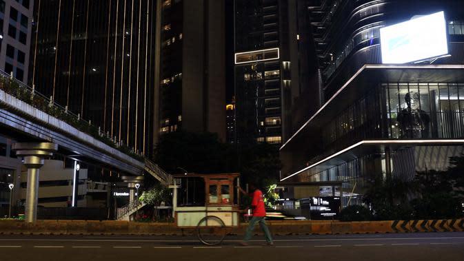 Pedagang mendorong gerobaknya di Jalan Jenderal Sudirman, Jakarta, Kamis (2/4/2020). Pemerintah menetapkan Pembatasan Sosial Berskala Besar dengan membatasi kegiatan tertentu penduduk di wilayah yang diduga terinfeksi COVID-19. (Liputan6.com/Helmi Fithriansyah)