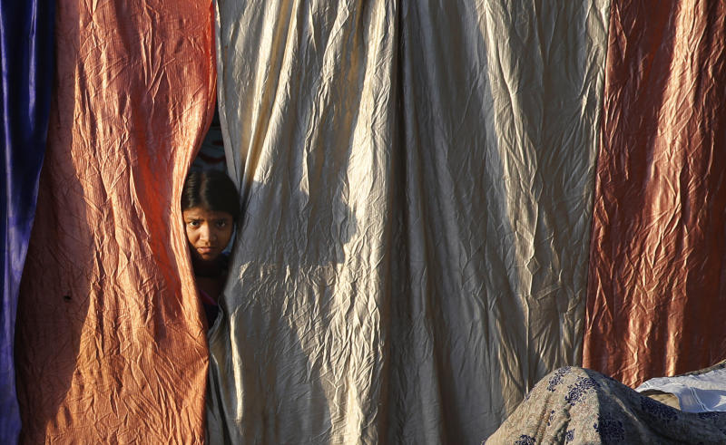 A girl living on the roadside looks out from her makeshift home during a lockdown to control coronavirus spread, in Prayagraj, India, Wednesday, March 25, 2020. The world's largest democracy went under the world's biggest lockdown Wednesday, with India's 1.3 billion people ordered to stay home in a bid to stop the coronavirus pandemic from spreading and overwhelming its fragile health care system as it has done elsewhere. The new coronavirus causes mild or moderate symptoms for most people, but for some, especially older adults and people with existing health problems, it can cause more severe illness or death. (AP Photo/Rajesh Kumar Singh)