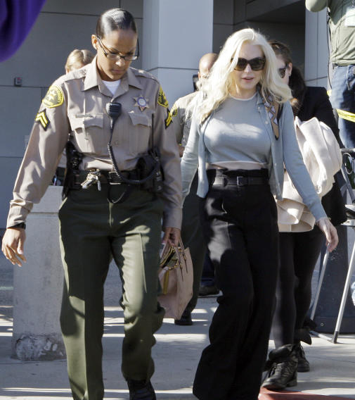 Lindsay Lohan leaves Los Angeles Superior Court after a probation progress hearing Tuesday, Jan. 17, 2012. Superior Court Judge Stephanie Sautner told the actress she is on track to complete strict terms of her probation by the end of March. The 25-year-old is required to do cleanup duty at the morgue and attend therapy sessions. (AP Photo/Reed Saxon)