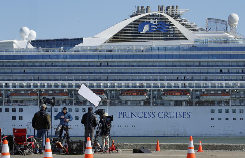 A media crew prepare to film with the Grand Princess cruise ship in the background at the Port of Oakland Thursday, March 12, 2020, in Oakland, Calif. California Gov. Gavin Newsom says nearly 500 passengers remain aboard the cruise ship. In addition to the 21 people who previously tested positive while aboard, Newsom says at least two more people have tested positive after leaving. (AP Photo/Ben Margot)