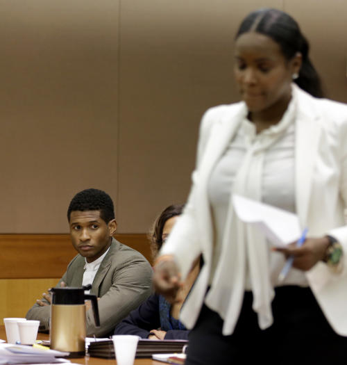 R&B singer Usher, left, looks on as ex-wife Tameka Foster Raymond takes the witness stand during a child custody hearing, Friday, Aug. 9, 2013, in Atlanta. Foster Raymond requested the hearing earlier this week after the former couple's son got caught in a pool drain while in the care of the Grammy winner's aunt. (AP Photo/David Goldman)