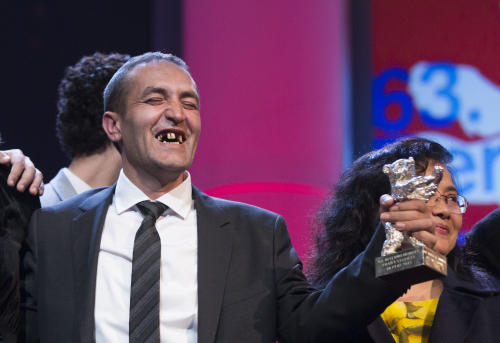 FILE - This is a Saturday, Feb. 16, 2013 file photo of actor Nazif Mujic with his Silver Bear Best Actor award for his role in An Episode In the Life of an Iron Picker, at the closing ceremony at the 63rd edition of the Berlinale, International Film Festival in Berlin. People in the Gypsy village of Poljice in Bosnia said they will never forget the night they almost fell off their chairs two months ago. Did they really hear the elegant woman on TV correctly? Could she really be talking about their neighbor, the toothless man who passed his days selling scrap metal? The camera switched to a frightened-looking Nazif Mujic. Yes it was him. THEIR Nazif _ who had just left Matt Damon and Jude Law in the dust to win the best actor award at the Berlin Film Festival.(AP Photo/Gero Breloer, File)