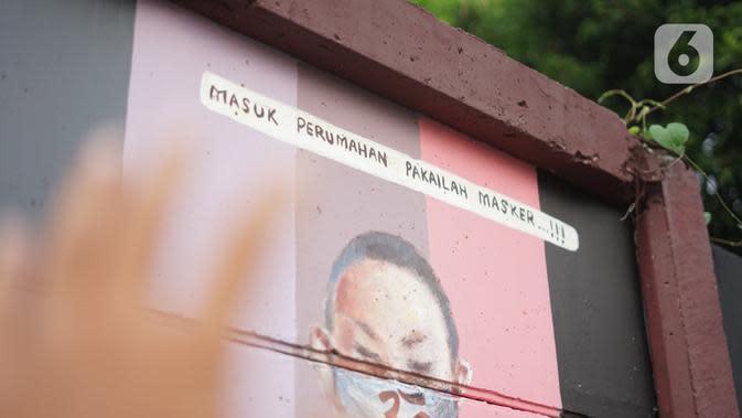 Mural bergambar simbol orang berdoa menggunakan masker di kawasan Juanda, Kota Depok, Jumat (26/6/2020). Mural yang dibuat warga tersebut bertujuan memberi edukasi untuk menggunakan masker sebagai salah satu pencegahan dan penyebaran COVID-19. (Liputan6.com/Immanuel Antonius)