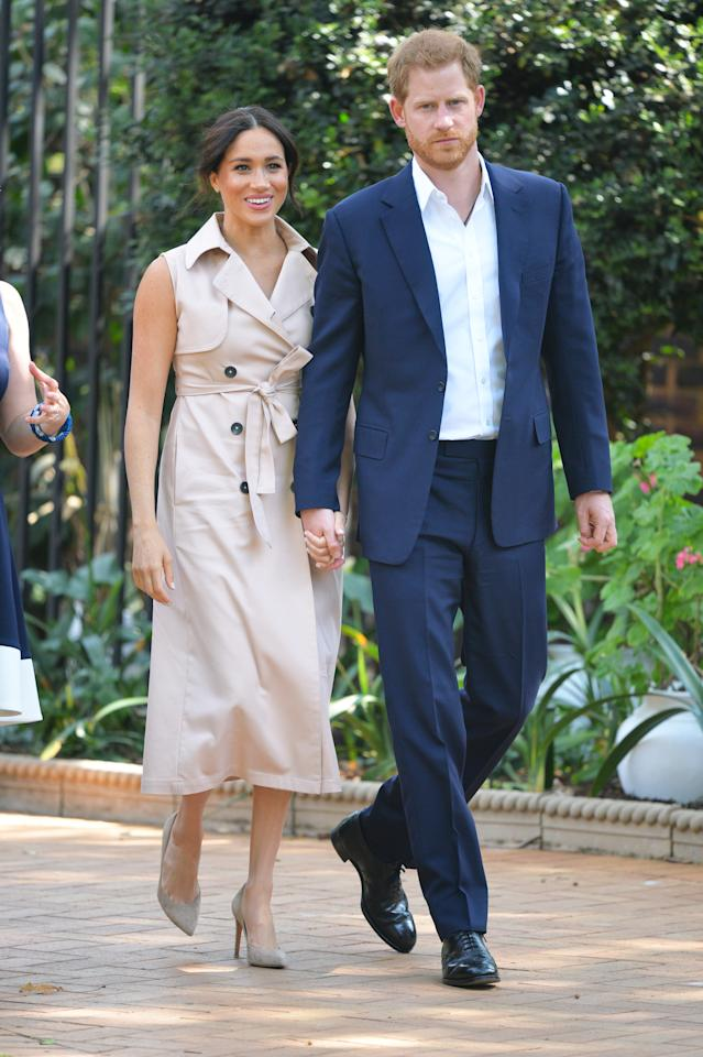 """Meghan's afternoon began meeting Graca Machel, widow of the late Nelson Mandela. Poignantly, Meghan chose to rewear her <a href=""""https://www.houseofnonie.com/store/p80/Sleeveless_Trench.html?"""">House of Nonie</a> sleeveless trench dress, which she first wore in 2018 to visit the Nelson Mandela Centenary Exhibition. <em>[Photo: Getty]</em>"""