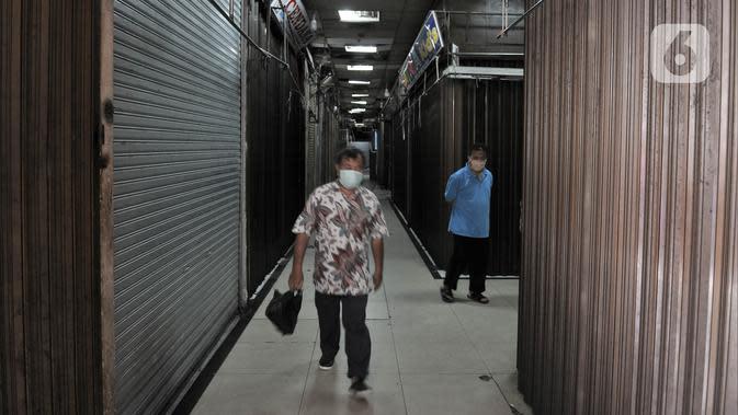 Pengunjung saat melintasi pertokoan yang tutup di Pasar Jatinegara, Jakarta, Kamis (26/3/2020). Pedagang yang masih tetap membuka toko pun mengeluh karena penjualan menurun hingga 80 persen. (merdeka.com/Iqbal S. Nugroho)