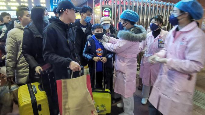 Petugas memeriksa suhu tubuh seorang penumpang di Stasiun Kereta Api Yingtan di Nanchang di Provinsi Jiangxi Tengah, China (22/1/2020). Sebanyak 17 orang meninggal akibat terinfeksi virus corona. (AFP Photo/STR)