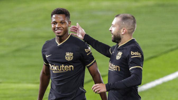 Pemain Barcelona, Ansu Fati (kiri), mendapat selamat dari rekan setimnya, Jordi Alba, setelah mencetak gol ke gawang Celta Vigo pada lanjutan Liga Spanyol, Jumat (2/10/2020) dini hari WIB. (AP/Lalo R. Villar)