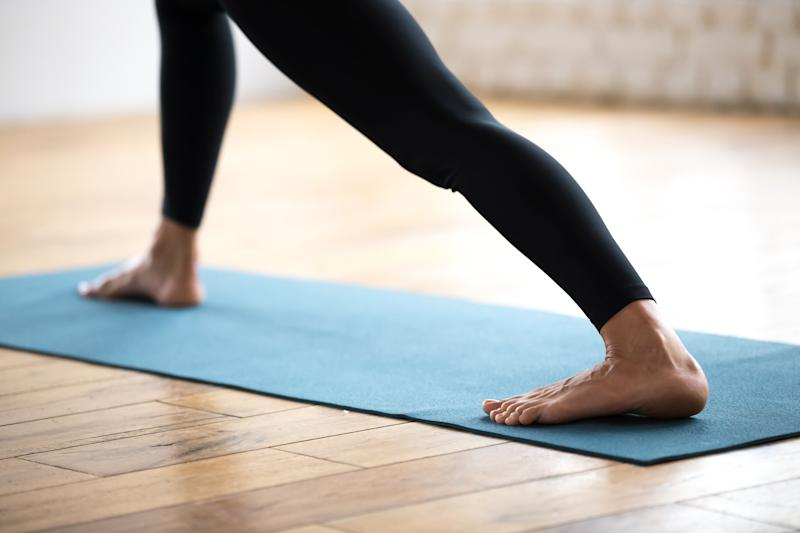 Sporty woman practicing yoga or fitness, doing stretch exercise in standing pose, working out, wearing sportswear, black pants, indoor close up, yoga studio. Well being concept