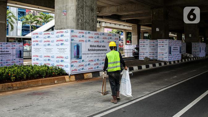 Seorang pekerja melintas di bawah Stasiun MRT Haji Nawi, Jakarta, Minggu (4/10/2020). PT Mass Rapid Transit atau MRT Jakarta menyiapkan sejumlah pilar jalur MRT sebagai media iklan untuk mengembangkan bisnis di luar pendapatan tiket atau non-farebox. (Liputan6.com/Faizal Fanani)